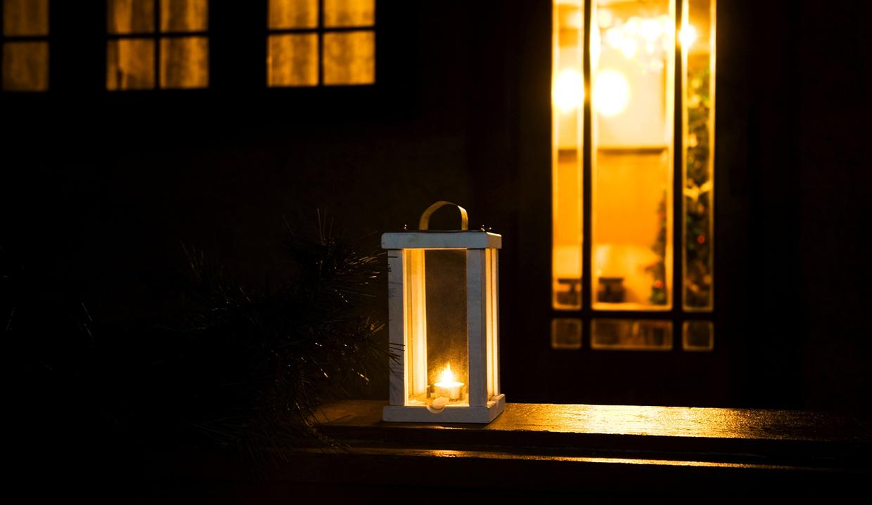 Kerze draussen nachts vor einem erleuchtetem Haus zu Weihnachten